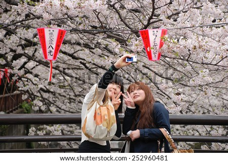 TOKYO, JAPAN - APRIL 5 : Tourist selfie with sakura flower taken April 5, 2009 in Naga Meguro area, Tokyo. This area is popular sakura spot in Tokyo with beautiful canal. - stock photo