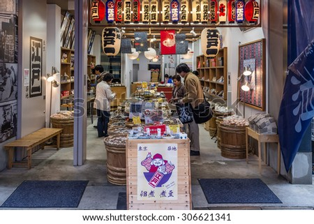 Tokyo, Japan - April 10: Unidentified shoppers buy local products in one of the typical small shops located in the outer area of the Tsukiji Fish Market, in Tokyo, Japan; on April 10, 2015 - stock photo