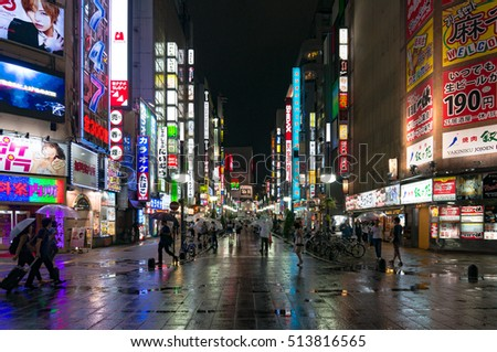 Tokyo, Japan - August 29, 2016: Night Shinjuku with people and bright advertising. Text in Japanese advertises different goods and services