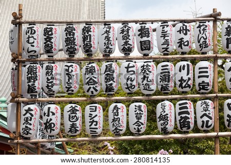 TOKYO, JAPAN - CIRCA APRIL, 2012: Many white and black paper lanterns with Japanese characters are in Sensoji shrine. The Senso-ji is an ancient Buddhist temple located in Asakusa district - stock photo