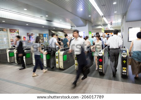 TOKYO, JAPAN-CIRCA JULY, 2014:People passing the gate. Commutor trains are the main mode of transportation in Tokyo. - stock photo
