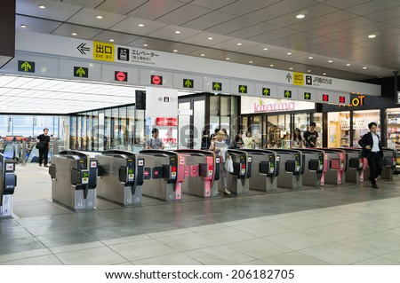 TOKYO, JAPAN - CIRCA JULY, 2014: People passing the gate. Commutor trains are the main mode of transportation in Tokyo. - stock photo
