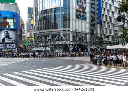 TOKYO, JAPAN - CIRCA MAY 2014: Pedestrians crossing the busiest crosswalk in the world in the Shibuya district in Tokyo, Japan. - stock photo