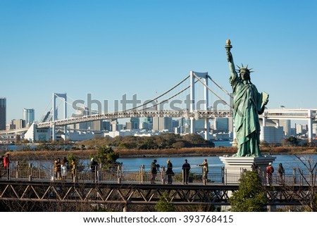 Tokyo, Japan -December 18, 2015:  Tourists at an elevated walkway in Odaiba enjoying the clear view of Tokyo Bay. The Statue of Liberty and the Rainbow Bridge in a view.  - stock photo