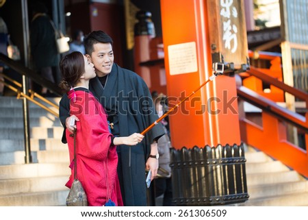 TOKYO, JAPAN - FEBRUARY 3, 2015: An unidentified couple go to Sensoji Temple located in Asakusa. They are using selfie stick for self portrait photo. - stock photo