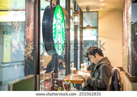 TOKYO,JAPAN - FEBRUARY 11,2015: Man sitting at Starbucks.It is an US global coffee company, the largest coffeehouse company in the world. - stock photo