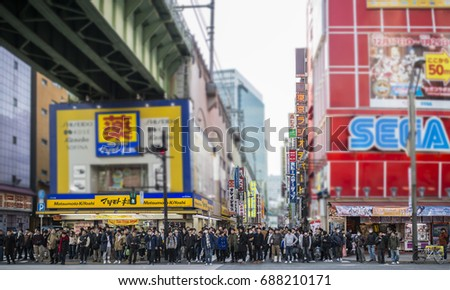 TOKYO, JAPAN - JANUARY 2, 2017: Crowds pass below colorful signs in Akihabara. The historic electronics district has evolved into a shopping area for video games, anime, manga, and computer goods.