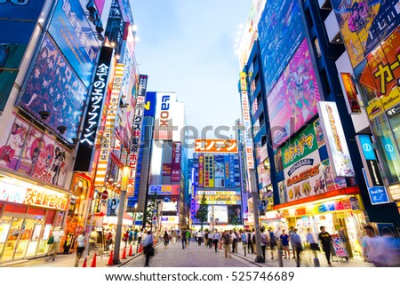 Tokyo, Japan - July 29, 2015: Bright neon lights and billboard advertisements on building sides in busy Akihabara electronics hub during dusk blue hour on a summer night in downtown. Horizontal