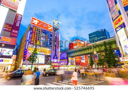 Tokyo, Japan - July 29, 2015: Hectic hustle and bustle of main street in Akihabara among bright neon billboards and store signs at blue hour on summer evening in downtown
