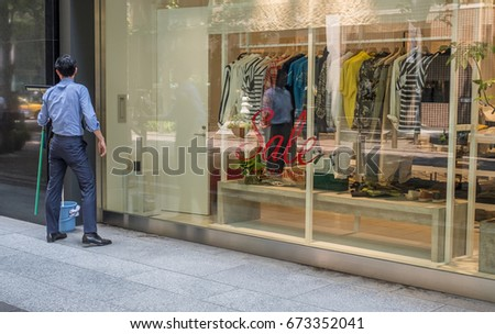 TOKYO, JAPAN - JULY 8TH 2017. Unidentified man at the luxury stores front in Nakadori Street in Marunouchi business district.