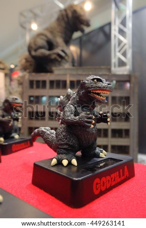 TOKYO, JAPAN - JUNE 29, 2016 : Godzilla on red carpet with abstract blur background of giant Godzilla larger than human scale. Godzilla or Gojira is a worldwide pop culture icon, originated from Japan - stock photo