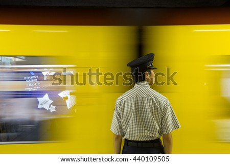 TOKYO, JAPAN - June 20 2016: Subway attendant and fast moving train. The Tokyo subway system handles 8 million passengers per day. In Tokyo, Japan 2016 - stock photo