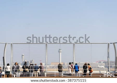 Tokyo, Japan - March 4 2016: People looking at the sky at the observation deck of Haneda International Airport in Tokyo, Japan. - stock photo