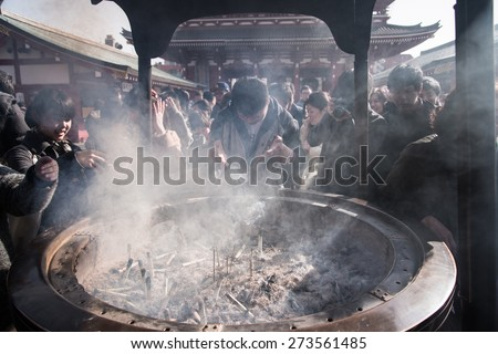 TOKYO, JAPAN - March 28 2015: People pray at Senso-ji Temple in Tokyo,Japan. The Senso-ji Temple is the symbol of Asakusa and one of the most famed temples in Japan. - stock photo