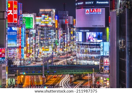 TOKYO, JAPAN - MARCH 19, 2014: Shinjuku district illuminated at night. The district is a renown night life center. - stock photo