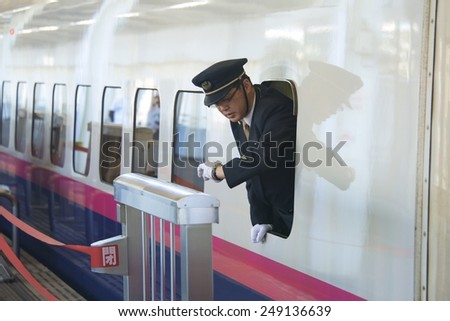 TOKYO, JAPAN - NOV 10: Shinkansen (Bullet Train) conductor checks time for prompt departure at Tokyo station, on November 10, 2014, in Tokyo, Japan. Shinkansen trains are known for being punctual. - stock photo