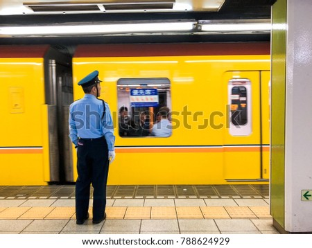 TOKYO, JAPAN - NOVEMBER 14, 2017: A worker watching Tokyo Metro train leaving the station.
