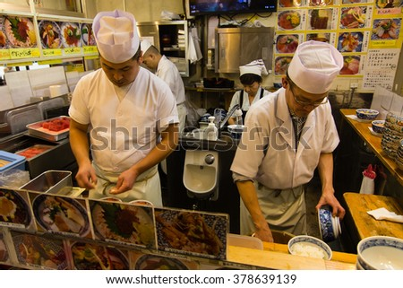 Tokyo, Japan - November 23, 2015: Two chefs preparing lunch for customers in a restaurant at Tsukiji market in Tokyo.