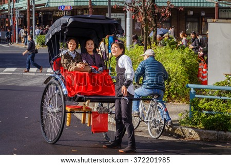 TOKYO, JAPAN - NOVEMBER 15, 2015: Unidentified rickshaw drivers with passengers in Asukusa station nearby Sumida river - stock photo