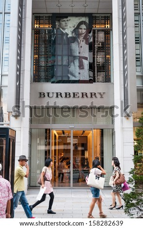 TOKYO, JAPAN - SEPTEMBER 22: Shoppers and tourists pass by a Burberry store in Ginza on September 22, 2013 in Tokyo, Japan. - stock photo