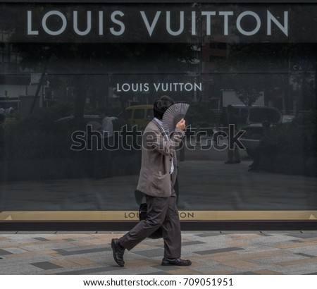 TOKYO, JAPAN - SEPTEMBER 1ST, 2017.  Japanese white collar workers or salaryman walking in front of Louis Vuitton outlet at Tokyo station.