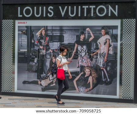 TOKYO, JAPAN - SEPTEMBER 1ST, 2017. Woman walking in front of Louis Vuitton outlet at Tokyo Station.
