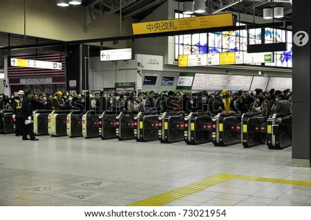 TOKYO - MAR 12: All trains and subway trains have stopped because of the ongoing earthquakes and people are waiting for trains to take them home on March 12, 2011 in Tokyo, Japan. Most have spent the night on the station. - stock photo