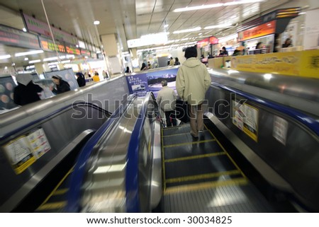 TOKYO - MARCH 22: A woman on escalator enters Tokyo metro at Shinjuku station on March 22, 2009 in Tokyo. With 3.64 million people per day in 2007 Shinjuku is the busiest train station in the world. - stock photo