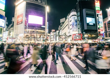 TOKYO - MARCH 31, 2016 : Pedestrians walk at Shibuya Crossing during the holiday season. The scramble crosswalk is one of the largest in the world.  - stock photo