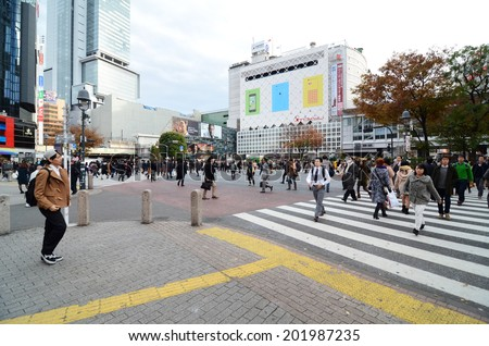 TOKYO - NOVEMBER 28: Crowds of people crossing the center of Shibuya in November 28 2013, the most important commercial center in Tokyo, Japan  - stock photo