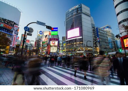 TOKYO - NOVEMBER 28: Pedestrians at the famed crossing of Shibuya district November 28, 2013 in Tokyo, Japan. Shibuya is a fashion center and nightlife area.  - stock photo