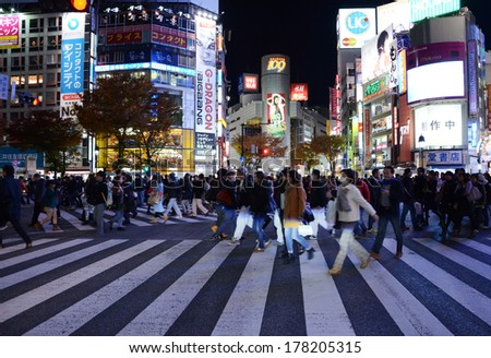 TOKYO - NOVEMBER 28: Pedestrians at the famed crossing of Shibuya district November 28, 2013 in Tokyo, JP. Shibuya is a fashion center and nightlife area.  - stock photo