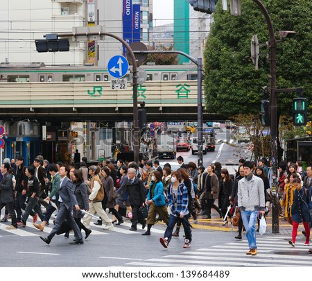 TOKYO - NOVEMBER 12: People crossing the street at Shibuya crossing in Tokyo on November 12, 2012. This location is one of busiest in Tokyo and recognized thanks to being featured in multiple films. - stock photo