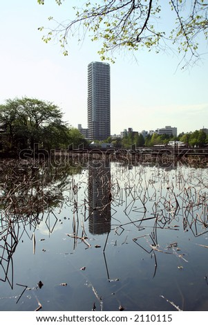 Tokyo office building reflected in a lake. - stock photo