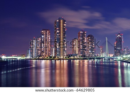 Tokyo skyline by night in modern Tsukishima district with scenic water reflection in Sumida river waters - stock photo