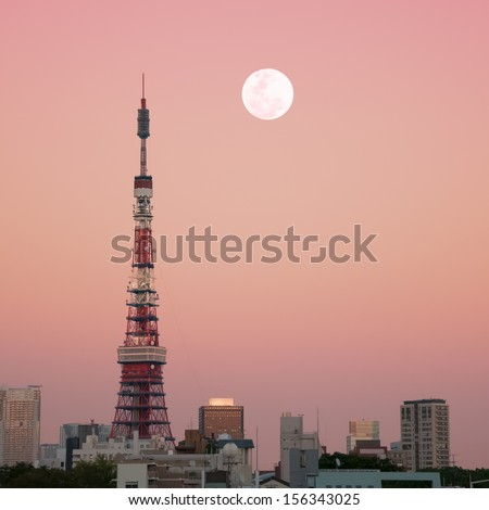 Tokyo Tower at dusk with the full moon rising. - stock photo