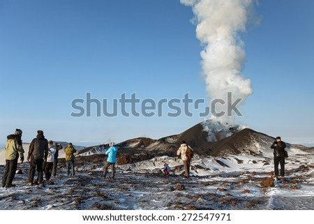 TOLBACHIK VOLCANO, KAMCHATKA, RUSSIA - FEBRUARY 2, 2013: Tourists watching the eruption of active Tolbachik Volcano, ejecting lava, ash, steam and gas. Russia, Far East, Kamchatka Peninsula. - stock photo