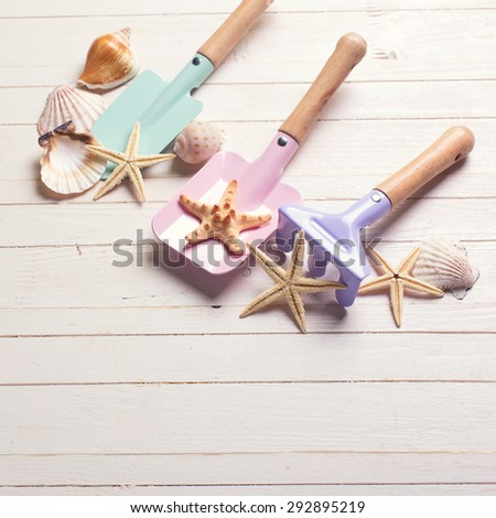 Tolls  for kids for sand and sea object on white  painted wooden background. Place for text. Square image. - stock photo