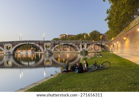 TOLOUSE, FRANCE - OCTOBER 3 2014: Groups of people enjoying the sunset near one of the beautiful bridges crossing the Garonne river passing-through the city of Toulouse. - stock photo