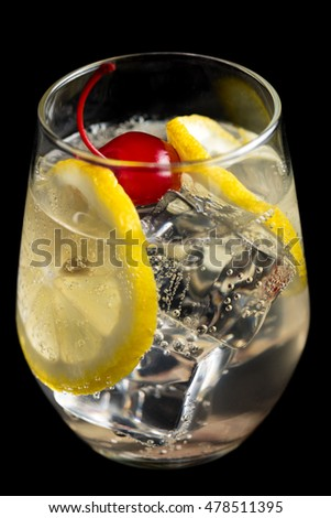 Tom Collins cocktail with lemon on black background