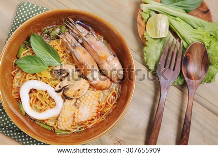 Tom Yam Kung soup with noodles ,Tom Yum Nam Khon - Creamy Thai soup with prawns and mushrooms garnished with coriander leaves and served with lime wedges. Overhead shot. - stock photo