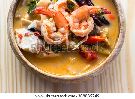 Tom Yam Kung (Thai cuisine) on a wooden table - stock photo