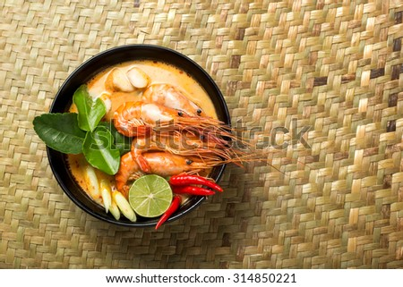 Tom Yum Goong spicy soup traditional thai food cuisine in Thailand on mat wicker background  - stock photo