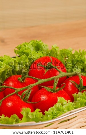 Tomate with salad in basket on wooden table - stock photo