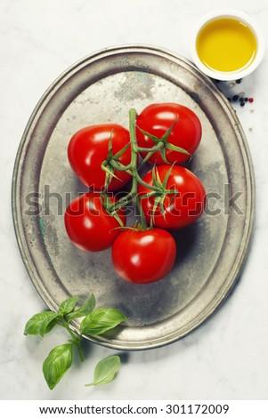Tomato and fresh italian ingredients on vintage plate - stock photo