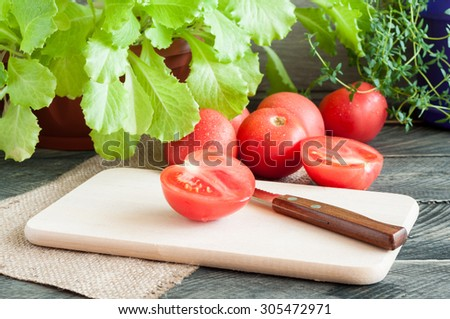 Tomato and knife on board. Lettuce and thyme on an old wooden table. Ingredients for salad - stock photo
