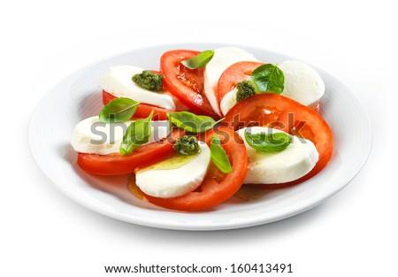 tomato and mozzarella salad on white plate - stock photo