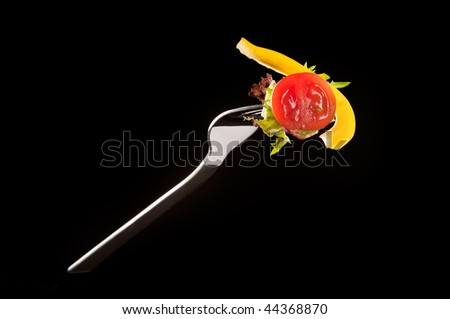 Tomato and pepper on a fork isolated on black - stock photo