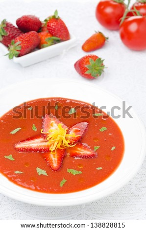 tomato and strawberry gazpacho in a plate, fresh berries and tomatoes in the background, vertical - stock photo