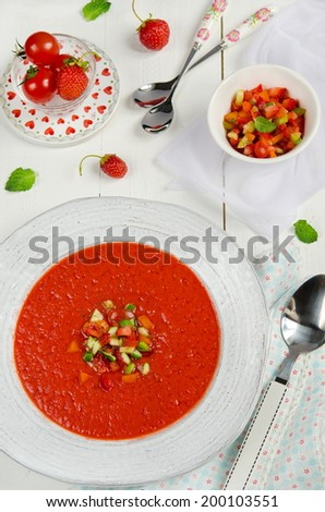 Tomato and strawberry gazpacho in a plate on a white wooden background - stock photo